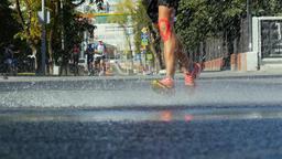 young men marathon runs through a puddle, splashing water around athlete Footage