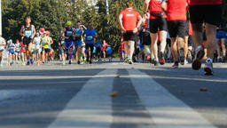 large group of marathon runners running through streets of city to towards each  Footage
