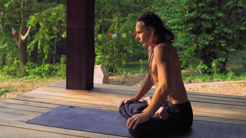 Yogi sitting on a mat in the park and an exercise Footage