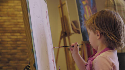The little girl in a pink shirt paints paints on canvas Footage