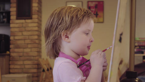 The little girl paints on a canvas, leaving and waiting for approval Footage