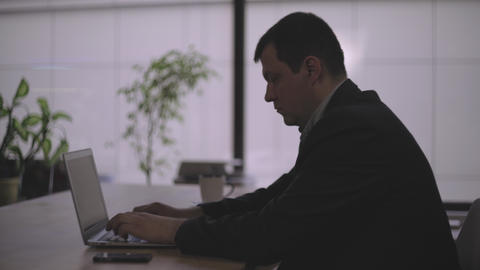 Middle-aged man in the office at the table, working on the computer Footage