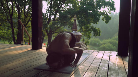 A man practices yoga on a wooden platform Footage
