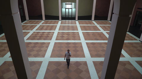Middle-aged man standing in a large circle with columns, talking on the phone Footage