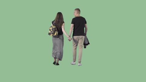 Beautiful couple in summer clothes are strolling holding hands. Alpha matte Footage