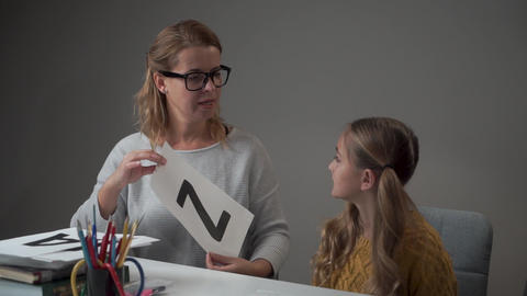 Portrait of a young Caucasian tutor in eyeglasses showing card with letter Z to Live Action