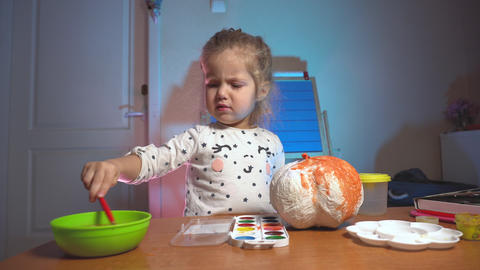 Little girl colorizing fake craft pumpking in orange color Live Action