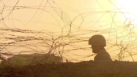 Silhouette of a soldier in a helmet who guards a checkpoint in the desert, fences and barbed wire, Archivo