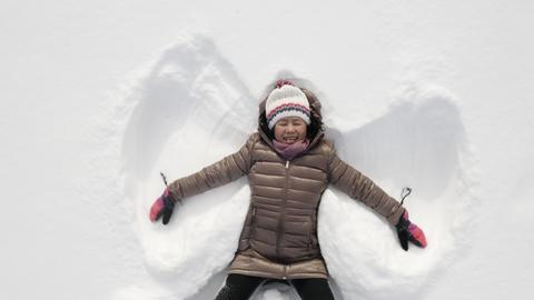 Woman making a snow angel Archivo