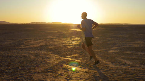 Athletic man working out with battle ropes on a dry lake at sunset Live Action