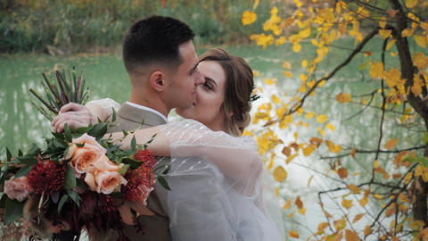 Close-up portrait of Groom and bride hugging near a lake in autumn forest among Live Action