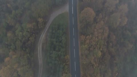 Drone following white car speeding on dark and misty mountain road ビデオ