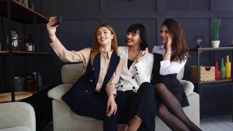 Three young girls are sitting on a sofa. Girlfriends take a selfie. Women at a Footage