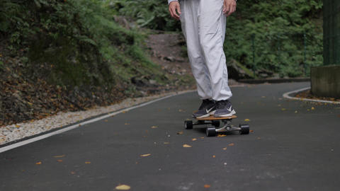 Skater legs riding on skateboard on winding road through mountain forest. Close up man riding on ビデオ