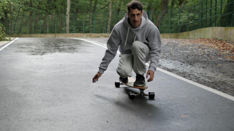Skateboarder legs riding on longboard on winding road through mountain forest. Close up man riding ビデオ