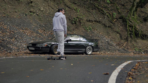 Skater riding on longboard on winding road through mountain rain forest. Close up man riding on ビデオ