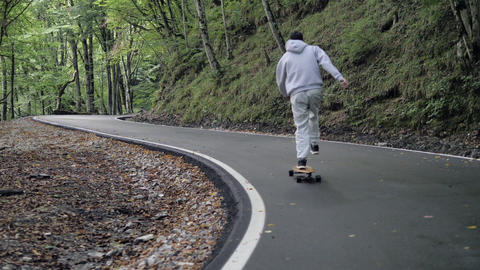 Skater on grey hoody ride cruise longboard on winding road through mountain forest. Close up man ビデオ