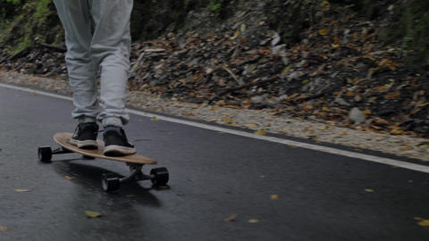 Skateboarder legs riding on skateboard on winding road through mountain forest. Close up man riding ライブ動画