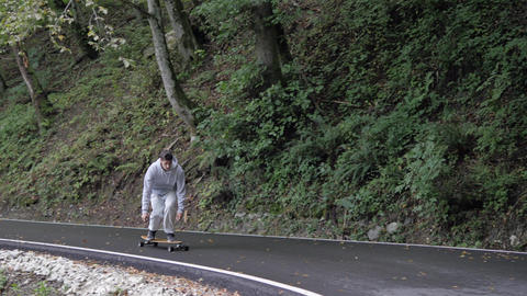 Man skateboarder riding on cruise longboard downhill on raw rainy road through mountain forest. ビデオ