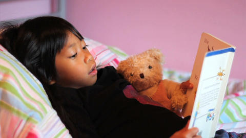 Little Asian Girl Reads Story Book To Teddy Bear Stock Video Footage