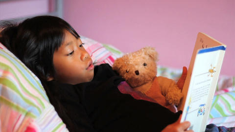 Little Asian Girl Reads Story Book To Teddy Bear Footage