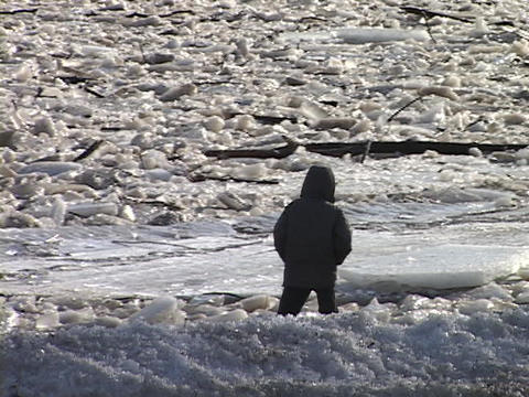 A child throws rocks across a frozen river Footage