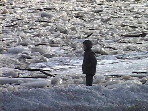 A child throws rocks across a frozen river Stock Video Footage
