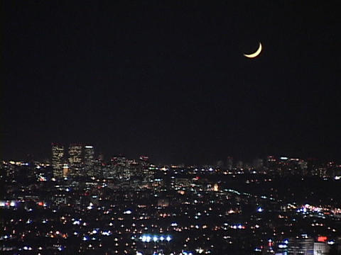 A new moon dominates the night sky over the city of Los... Stock Video Footage