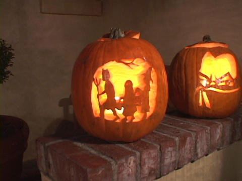 Jack-o-lanterns glow on a brick step Stock Video Footage