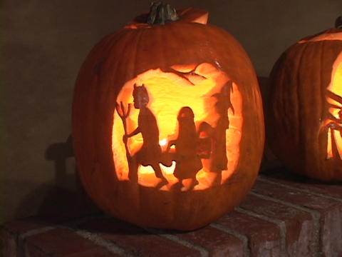 Jack-o-lanterns glow on a brick step Footage