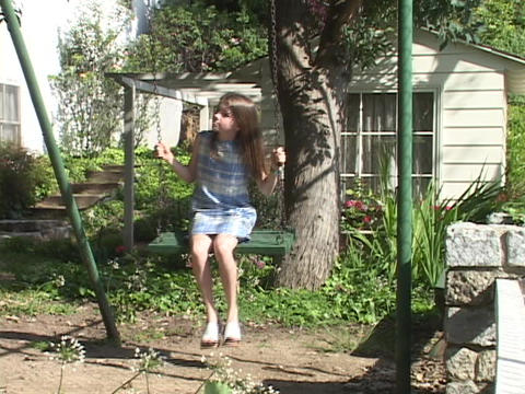 A girl swings in front of small cottage Footage