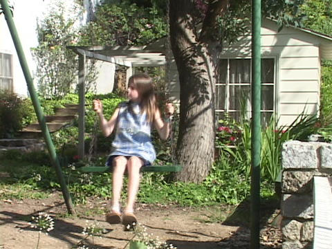 A girl swings in front of small cottage Stock Video Footage