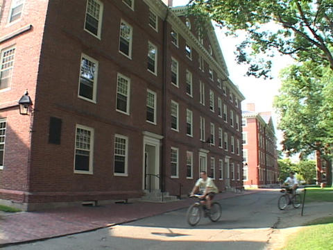 Students ride bicycles in front of a Harvard classroom building Footage