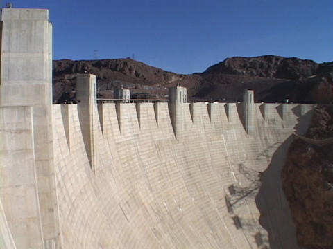 Mountains peak over the majestic Hoover Dam Stock Video Footage