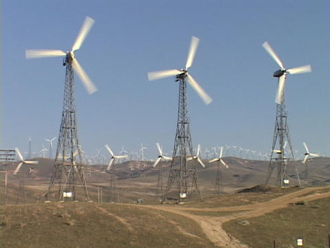 Large windmills spin at a wind-farm Stock Video Footage