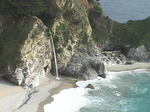 Gentle waves and a waterfall wash the sand on the shore of a rocky Big Sur coastline Footage