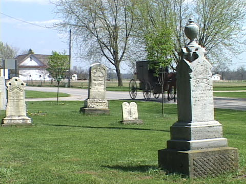An Amish horse carriage passes a cemetery Stock Video Footage