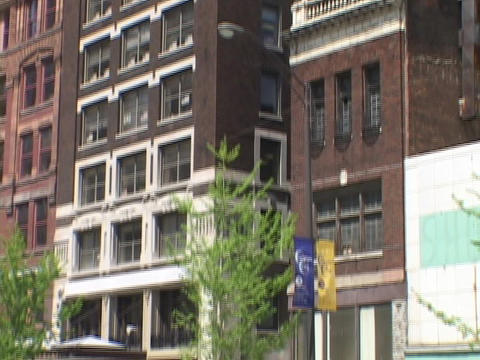 Brownstone office buildings rise from a city street Stock Video Footage