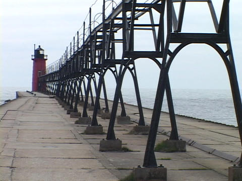 A lighthouse stands at the end of a pier in Grand Haven, Michigan Footage