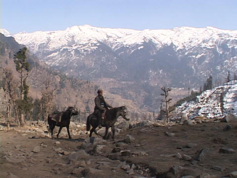 A man rides his horse across a rocky field Footage