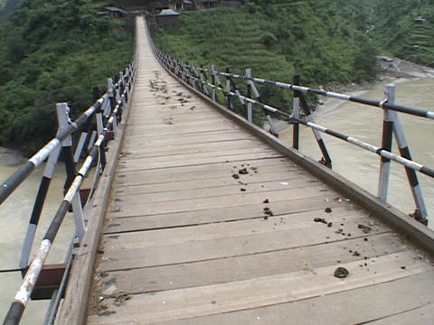 Men with horses cross a high suspension bridge in the... Stock Video Footage