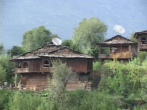 Satellite dishes sit atop vintage huts Stock Video Footage