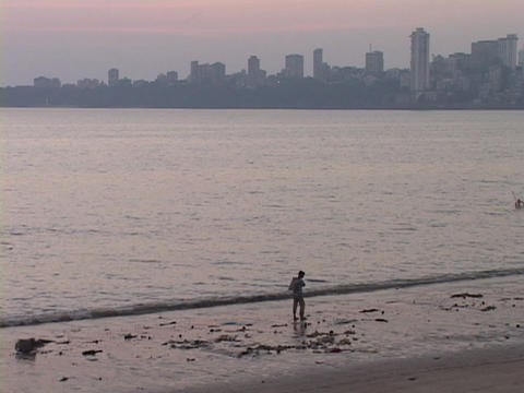A person walks along the beach near Mumbai, India Footage