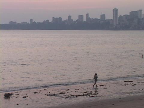 A person walks along the beach near Mumbai, India Stock Video Footage