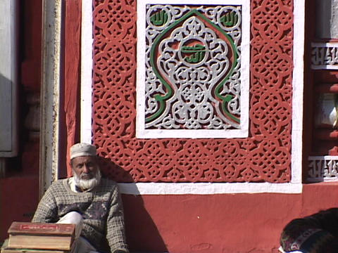 A Muslim man sits outside mosque after prayer Stock Video Footage