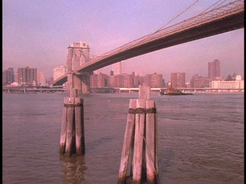 The Brooklyn Bridge towers over New York City's waterfront Stock Video Footage