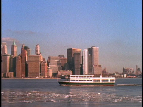 A ferry boat floats past the New York City skyline Stock Video Footage