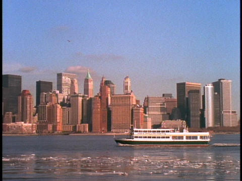 A ferry boat floats past the New York City skyline Footage