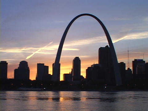 The silhouetted St. Louis towers over the Mississippi River Stock Video Footage
