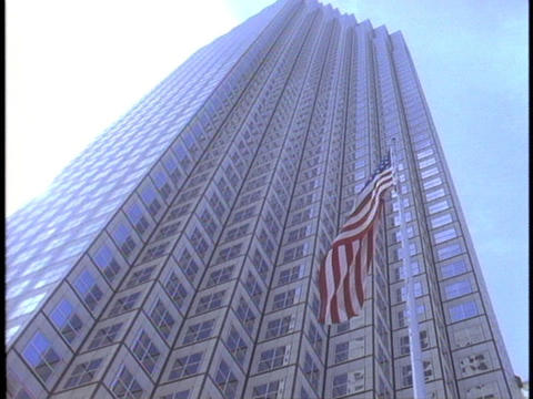 An American flag waves in the wind in front of a skyscraper Stock Video Footage